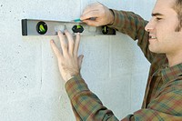 Man using level to draw line on wall