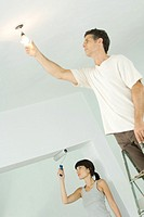 Woman painting with paint roller while man changes lightbulb