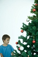 Boy standing near Christmas tree