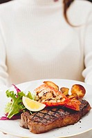 Grilled sirloin steak with lobster and roast potatoes