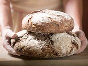 Hands holding two loaves of coarse rye bread