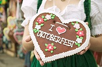Woman in national dress holding Lebkuchen heart at Oktoberfest