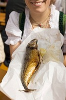 Woman holding Steckerlfisch fish on stick, Oktoberfest, Munich