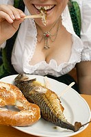 Woman eating Steckerlfisch & pretzel Oktoberfest, Munich
