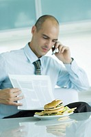 Man sitting at table with hamburger, reading newspaper and using cell phone