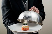 Butler serving salmon tartate on plate with dome cover