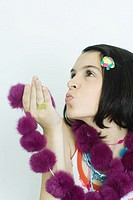 Teen girl holding up fur scarf, blowing kiss, portrait