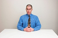 Young man in business shirt and tie sitting at an empty desk. Expression suggests surprise and nervousness, at an unusual request perhaps.
