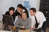 Businesspeople laughing at computer