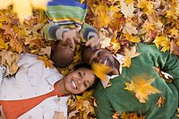 Family lying down in Autumn leaves