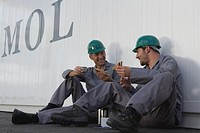 Two men eating lunch beside cargo container, wearing hard hats