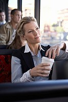 Woman holding disposable cup on bus
