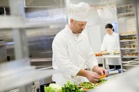 Two chefs in commercial kitchen focus on man in foreground