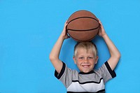 Portrait of boy holding basketball on head