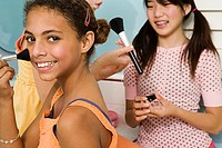 Two preteen girls applying makeup