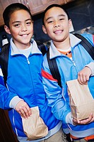 Boys wearing backpacks holding lunch bags