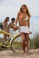 Woman in bathing suit standing with bike