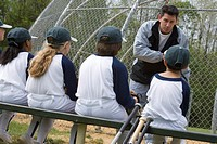 Coach talking to little league team
