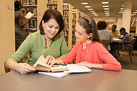 Mother helping daughter with homework in library