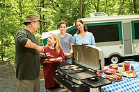 Family cooking outdoors at campsite
