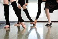 Ballet instructor adjusting girl´s foot in ballet class