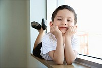 Boy in ballet class lying in window sill
