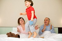 Grandchild jumping with grandparents sitting in bed