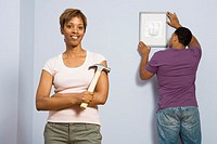 Man hanging picture on wall with woman holding hammer