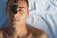 Man with hot stone massage rocks on his face