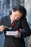 Businessman using cell phone and eating