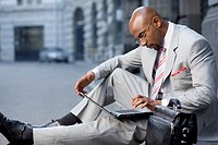 Businessman sitting on ground and using laptop