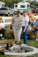 Senior Citizen campers roast hot dogs over an open camp fire