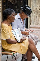 Couple of old people sitting in front of their home (Habana Vieja). Selling the newspaper 'Juventud revelde'. Havana. Cuba