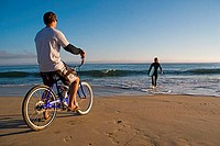 Young man riding a bicycle on the beach with young woman in the background