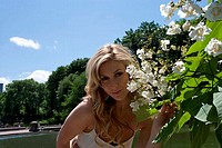 Portrait of a young woman smelling flowers, Central Park, Manhattan, New York City, New York, USA