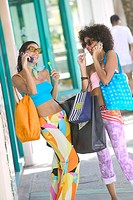 Women with shopping bags talking on mobile, outdoors