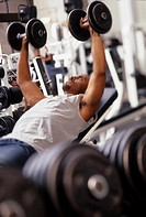 Man working out with hand weights in gym