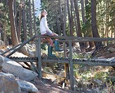 A young woman sitting on a wooden bridge in a forest