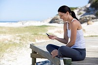 A young woman sitting on a beach using a mobile phone