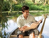 Young man sitting in a boat reading a newspaper