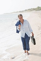 Relaxed businessman walking on beach