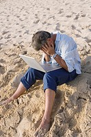 Dejected man using laptop on beach