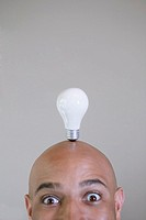 Businessman balancing a light bulb on head