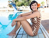 A young woman sitting by a swimming pool (thumbnail)