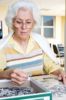 An elderly woman completing a jigsaw (thumbnail)