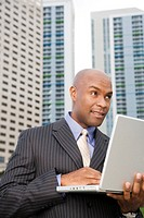 Businessman outside with a laptop computer