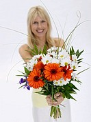 Woman holding bunch of flowers, portrait (thumbnail)