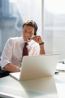 Business man sitting at desk, using head set