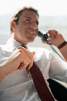 Business man holding pen, phoning