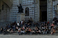 Large group of people sitting on steps in front of a building, IV November Square, Perugia, Umbria, Italy